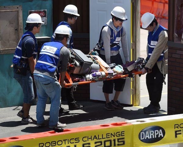 Команда NEDO-JDK из Японии переносят своего робота на носилках